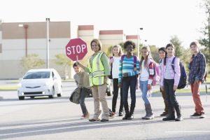 Kinder überqueren mit Crossing Gurad eine Straße