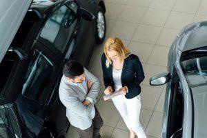 Verkäuferin berät Kunden beim Autokauf