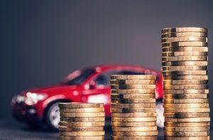 Auto hinter gestapelten Geldmünzen