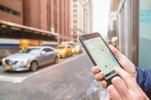 Fahrgast zeigt am Smartphone, wie Uber funktioniert